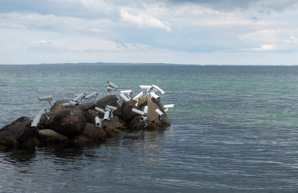 Security cameras perching on a seaside rock, like they were seagulls